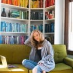 Ellie Roscher sitting on a couch in front of a shelf full of books