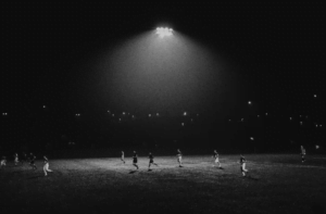 Players running across a soccer field at night